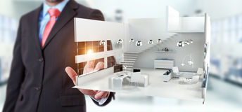 Businessman touching white 3D rendering apartment with his finge. Businessman on blurred background touching white 3D rendering apartment with his finger Royalty Free Stock Photography