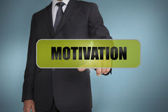 Businessman touching the word motivation written on green tag Stock Photos