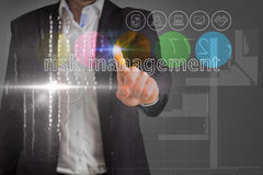 Businessman touching the words risk management on interface Stock Photo