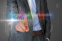 Businessman touching the words target your customers on interface Stock Image