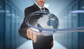Businessman touching world on futuristic interface with swirling lines Royalty Free Stock Images