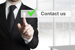 Businessman touchscreen button contact us Stock Photo