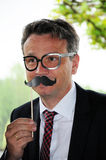Businessman with toy moustache and glasses Royalty Free Stock Photography