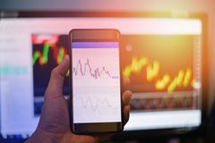 Businessman trading exchange board data on mobile screen / forex charts graph exchange on smart phone