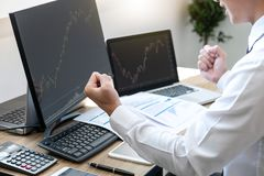Businessman trading stocks online, stock broker looking at graph working and analyzing with display screen and happy to deal on a royalty free stock images