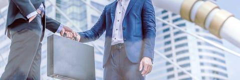 Businessman transfer deal, business black briefcase exchange urban city stock photo