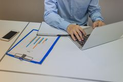 Businessman transfer information from documents to laptop stock image