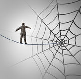 Businessman Trap. Business concept with a tightrope walker walking on a wire leading to a giant spider web as a metaphor for adversity and deception of being Stock Photography