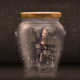 Businessman traped in jar with graph chart symbols concept Royalty Free Stock Photo