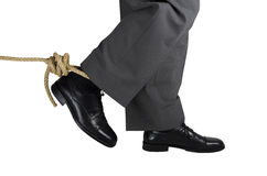 Businessman Trapped. Businessman caught in a rope that holds the foot. Isolated on white background Stock Images