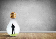 Businessman trapped in bulb Stock Photography