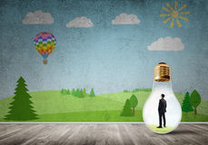 Businessman trapped in bulb Stock Images