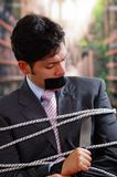 Businessman trapped in a chair with rope, with a black tape in his mouth, trying to cut the rope with a knife, in a Stock Photo