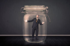 Businessman trapped into a glass jar concept Royalty Free Stock Photography