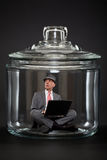 Businessman trapped inside a jar Stock Photography