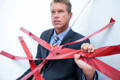 Businessman trapped by red tape Royalty Free Stock Photography