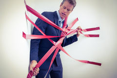 Businessman trapped by red tape Stock Photos