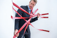 Businessman trapped by red tape Royalty Free Stock Photo