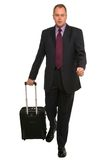 Businessman with travel luggage. Businessman walking along pulling some travel luggage Royalty Free Stock Image