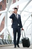 Businessman traveling with bag and talking on phone at station Royalty Free Stock Photo
