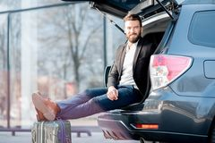 Businessman traveling by car. Businessman sitting with suitcase in the car trunk during the business travel. Business traveling by car concept Royalty Free Stock Photo