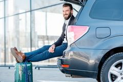Businessman traveling by car. Businessman sitting with suitcase in the car trunk during the business travel. Business traveling by car concept Stock Photography