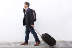 Businessman traveling with his suitcase and talking on cell phone outdoors. Full length side portrait of businessman traveling with his suitcase and talking on Royalty Free Stock Image