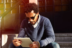 Businessman traveling, working in New York. Young black man siting on street, reading, working on electronic device. Royalty Free Stock Photo