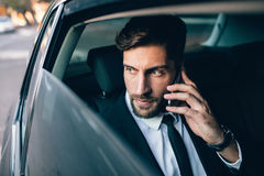 Businessman travelling by taxi and making phone call. Businessman talking on the mobile phone and looking outside the window while sitting on back seat of a taxi Royalty Free Stock Photography
