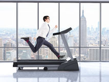 Businessman on treadmill. Businessman running on treadmill in interior with concrete floor and windows with New York city view. 3D Rendering Royalty Free Stock Photos