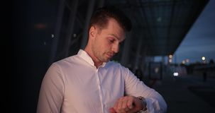 Businessman in a trip. Busy young handsome man looks around and on his armwatch waiting for a taxi outside.  stock video footage