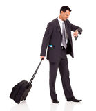 Businessman trolley bag. Businessman walking with trolley bag and looking at his watch Royalty Free Stock Photos