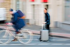 Businessman with trolley bag crosses the street. Motion blur picture of a businessman with trolley bag who crosses the street Stock Photography