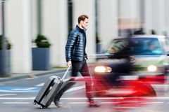 Businessman with trolley bag crosses the street. Motion blur picture of a businessman with trolley bag who crosses the street Royalty Free Stock Photography