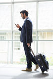 Businessman with trolley bag using mobile phone. At conference centre Royalty Free Stock Photography
