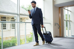 Businessman with trolley bag using mobile phone. At conference centre Royalty Free Stock Photo