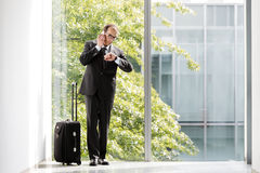 Businessman with trolley case looking at his watch and talking o. Formal wear Businessman with trolley case looking at his watch and talking on phone Royalty Free Stock Images