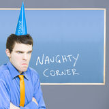 Businessman In Trouble Sitting In Naughty Corner Royalty Free Stock Images
