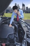 Businessman asking for a mechanic help. Businessman with a troubled car using a mobile phone asking for a help Royalty Free Stock Photo