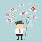 Businessman try to catch flying target. Royalty Free Stock Images