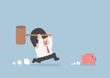 Businessman try to smashing piggy bank Royalty Free Stock Image