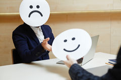 Businessman Trying on Different Masks Stock Photo
