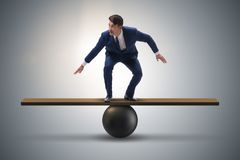The businessman trying to balance on ball and seesaw Royalty Free Stock Photos