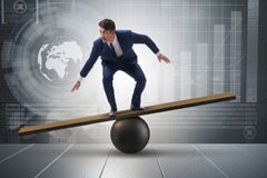 The businessman trying to balance on ball and seesaw Stock Images