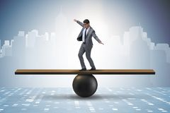 The businessman trying to balance on ball and seesaw Royalty Free Stock Photography