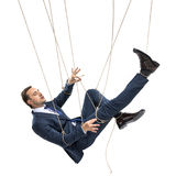 Businessman trying to break free while hanging on manipulating ropes. Isolated on white Royalty Free Stock Photography
