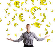 Businessman trying to catch falling down euros. Stock Photos