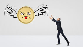 A businessman trying to catch a golden coin that flies away on its wings. Royalty Free Stock Image