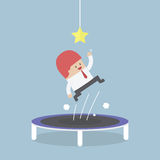 Businessman trying to catch the star by jumping on trampoline Royalty Free Stock Image