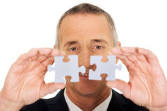 Businessman trying to connect puzzle pieces. Royalty Free Stock Image
